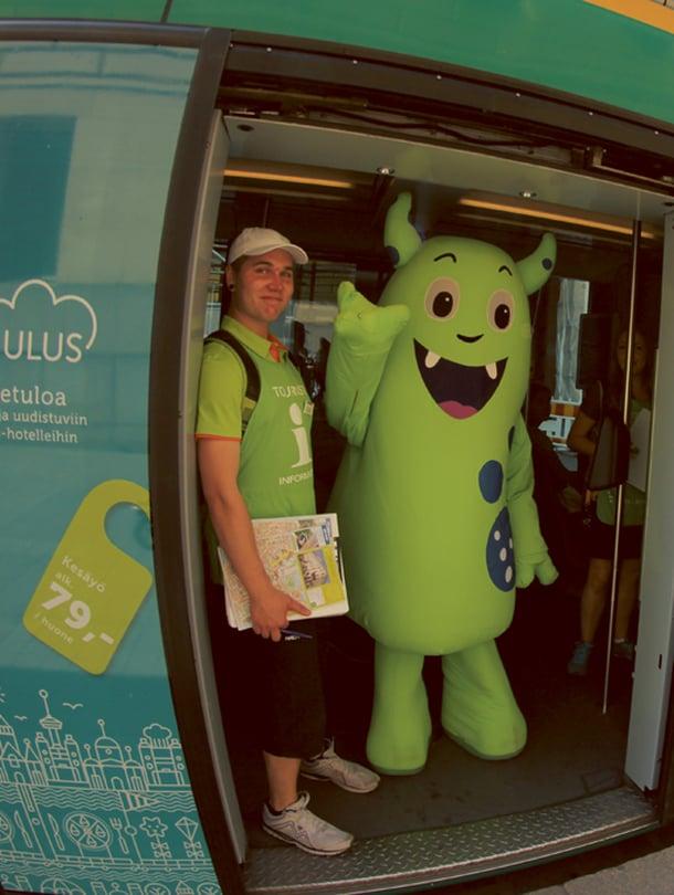 Helppi-hahmo auttaa turisteja Helsingissä.