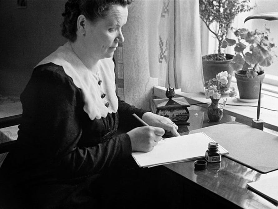 """Nainen kirjoittaa pöydän ääressä mustekynällä, 1940-luku. Kuva:<span class=""""photographer"""">Väinö Kannisto / Helsingin kaupunginmuseo</span>"""