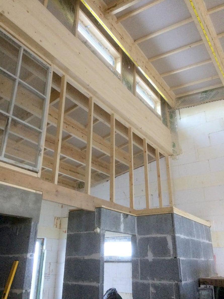 Asuinkerroksen väliseinä hahmottuu, alaosa on kiviseinää, yläosa kevytrakenteena.