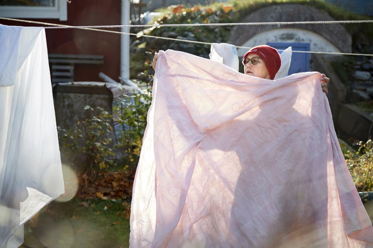 Utölainen Hanna Kovanen ripustaa pyykkiä kotinsa pihalla.