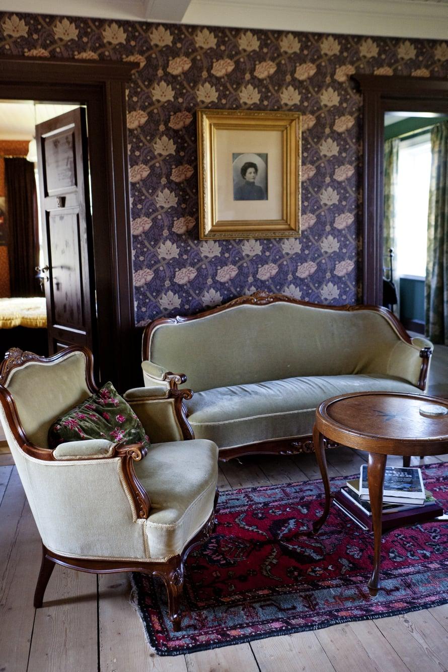 Sali on tapetoitu William Morrisin tyyliin. Emma-tädin kuva on kehystetty seinälle.