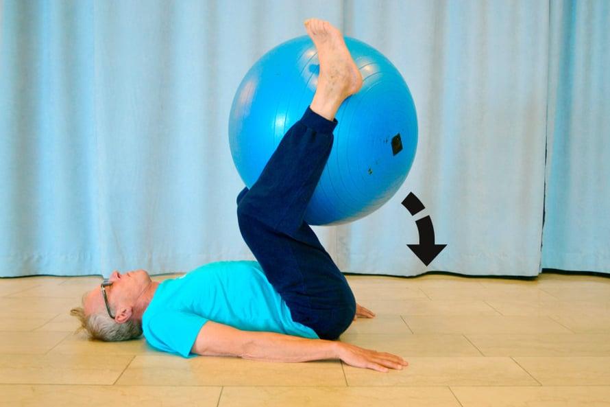 """KORSETTI KIREÄKSI. Asetu selinmakuulle, nosta jalat koukkuun ja purista jumppapallo tukevasti pohkeiden ja reisien väliin. Aseta kädet vartalon viereen kämmenpuoli lattiaa vasten. Nosta nyt jalat, takamus ja lantio sekä pallo rullaavalla liikkeellä mahdollisimman ylös siten, että ristiselkäsi kohoaa ainakin vähän irti lattiasta. Pysy tässä asennossa muutama sekunti ja laske pallo hitaasti alas. Liikkeen kuuluu tuntua vatsalihaksissa, joista eniten kuormittuvat syvät, ryhtiä ylläpitävät """"korsettilihakset""""."""