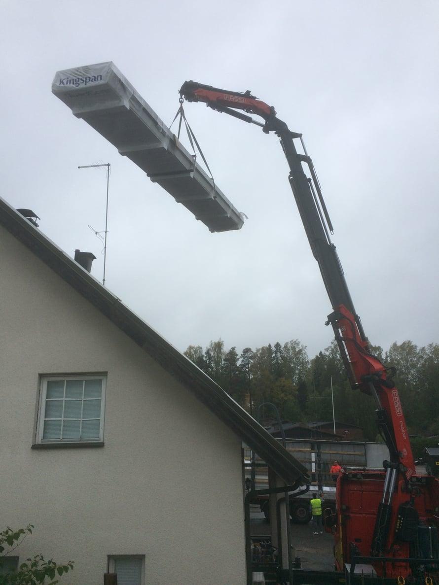 Nosturikuskimme Simon nostaa kattoelementtejä rekasta talon parvekkeelle.
