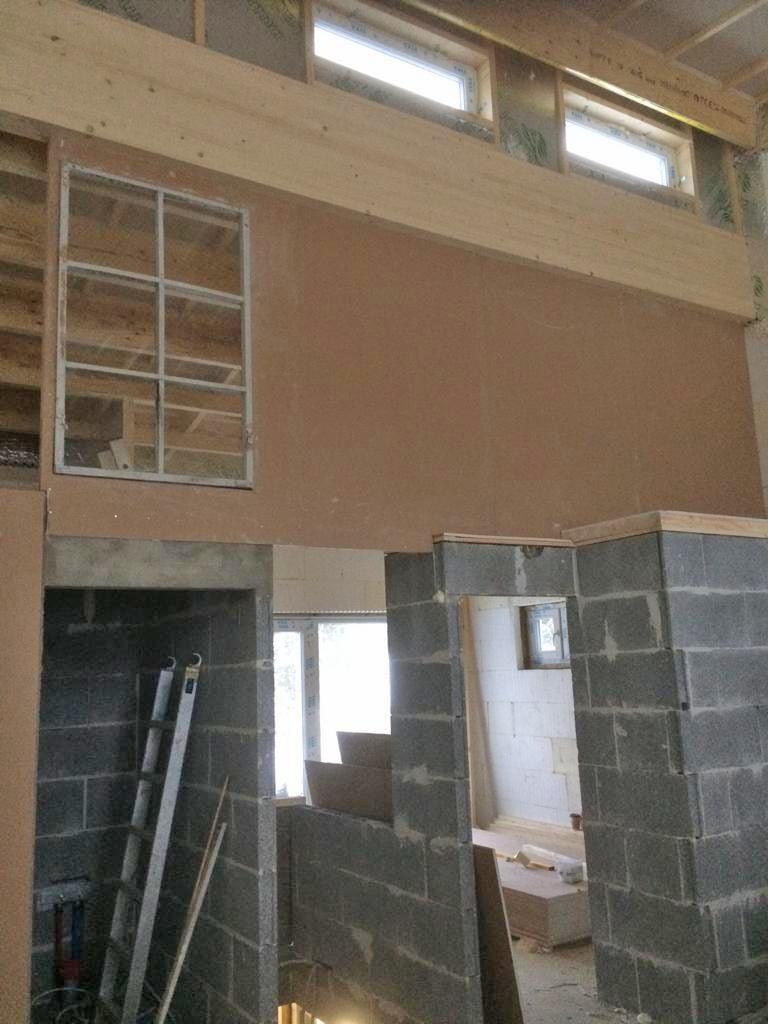 Asuinkerroksen seinäpinnat hahmottuvat jo selvästi. Kipsilevyn pinta on päällystetty ruskealla paperilla, jonka päälle tulevat saumatasoitukset ja pintaan valkoinen maali.