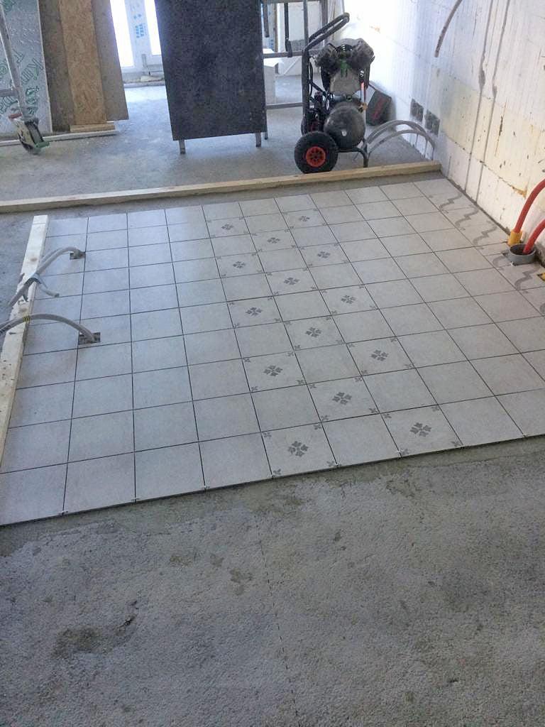 Keittiön lattialaatoitus on puolivälissä.