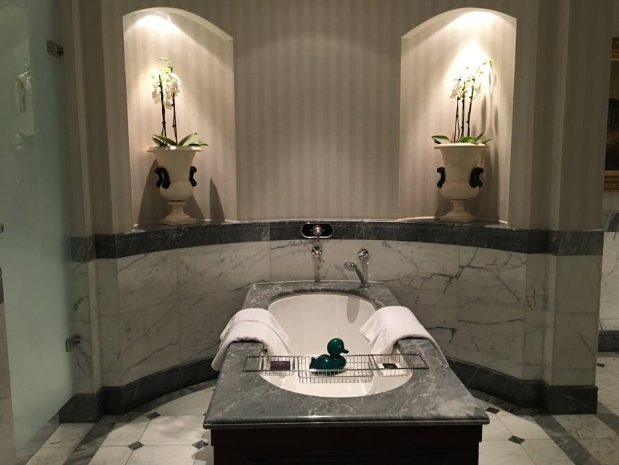 Ylellisessä kylpyhuoneessa on vihreä kylpyankka – kuten kaikissa muissakin Kämpin hotellihuoneissa.