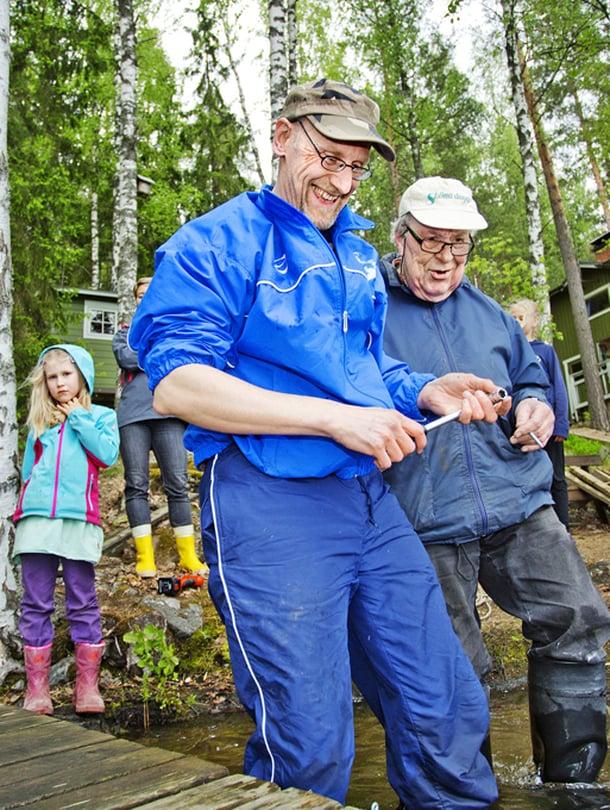 Otava Mäkinen, 14, ja Iben Madsen, 7,  oppivat tulevaa varten. Jukka Virtanen (edessä) ja Lauri Salonen asentavat laituria, Irma Salonen seuraa.