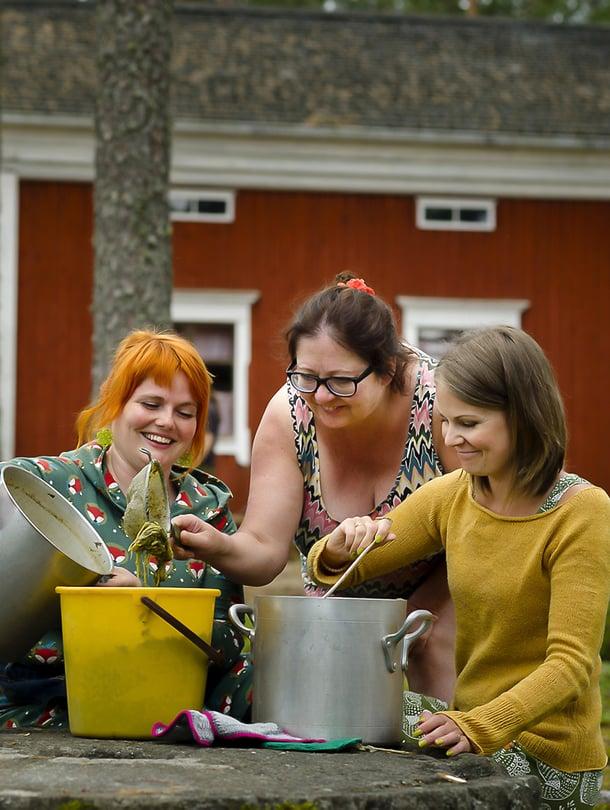 Noora Lappi, Sari Sheare ja Susanna Kuorikoski siivilöivät keitettyjä raparperinvarsia pois värjäysliemestä.