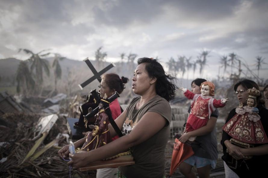 Philippe Lopez, Ranska, Agence France-Presse. Taifuunin runteleman kylän asukkaat uskonnollisessa kulkueessa Filippiineillä.