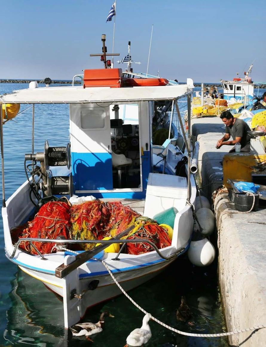 Kalastajat lasteineen saapumassa Tinoksen kaupungin keskustaan.
