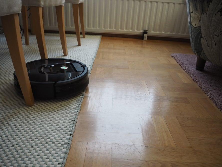 Roombaa voi auttaa esimerkiksi asettamalla tuolit jonoon niin, että se pääsee kerralla imuroimaan niiden alta. Kuvassa takana patterin edessä on majakka, joka esti robottia tällä kertaa menemästä nukkamatolle ja sohvien alle.