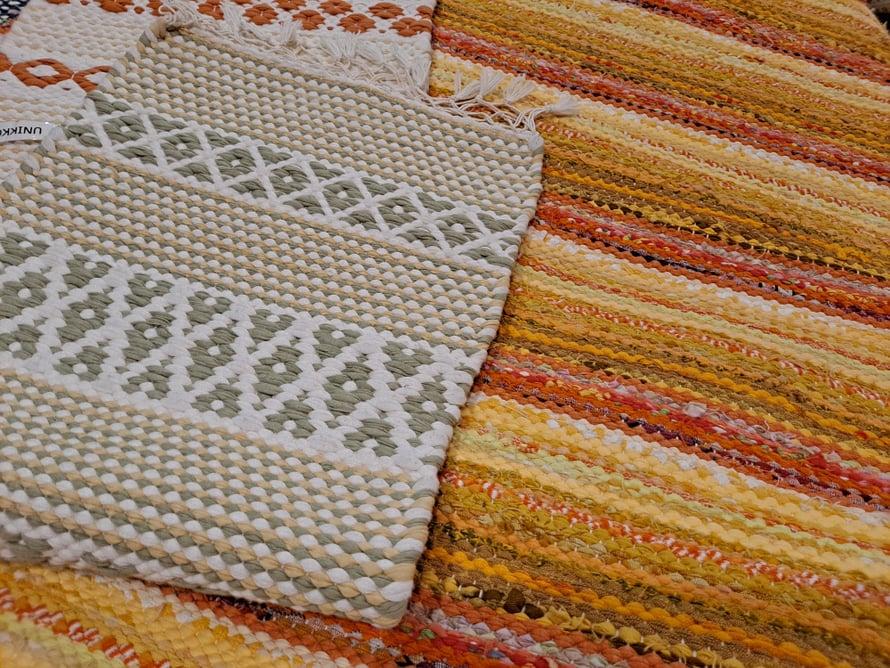 """Alla """"tavallista räsymattoa"""", jonka sidos on palttina, kudottuna kiikkalaiseen tapaan. Päällä ruusukassidoksinen mattonäyte, jossa on kuvioiden välillä palttinaa."""