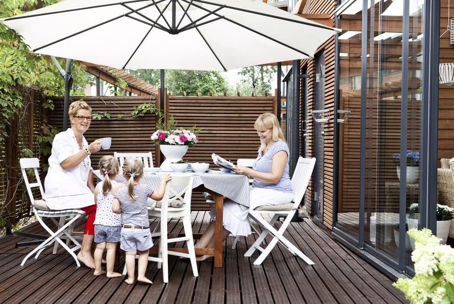 Aurinkovarjo suojaa patiolla ruokailijoita paahteelta.Anne, tytär Sanna ja Sannan tyttäret Alisa ja Ellen päiväkahveilla.
