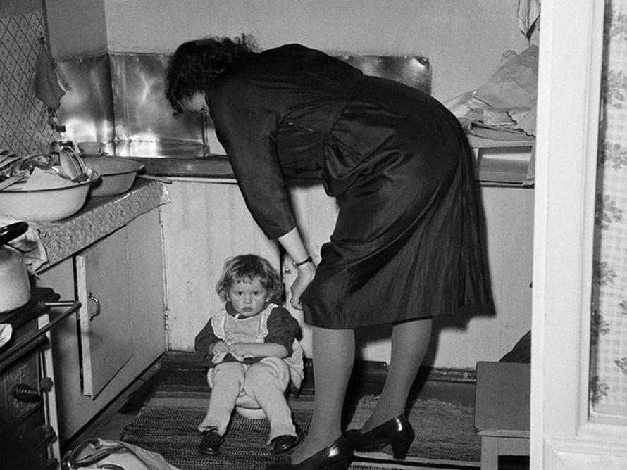 """Perhejuhla kotona 1950-luvulla, pieni tyttö istuu keittiössä potalla, äiti seisoo vieressä. Kuva: <span class=""""photographer"""">Väinö Kannisto / Helsingin kaupunginmuseo</span>"""