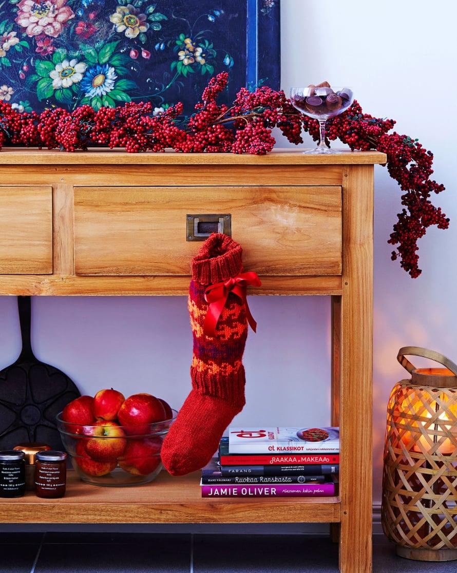 Marjaisa köynnös juhlistaa keittiön apupöydän. Vanha tarjotin toimii myös tauluna. Pikkuväki ilahtuu joulusukkaan piilotetuista makupaloista.