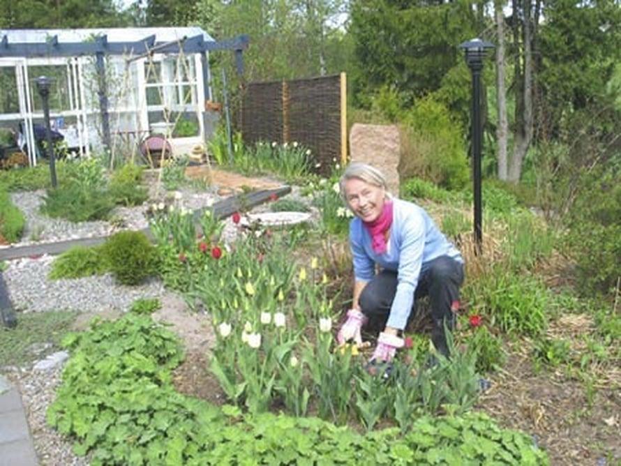 Irmeli Anttiroiko rehevässä puutarhassaan.