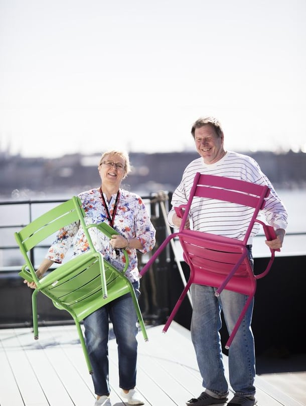 Leena Vahtera asettelee tuoleja Kotisataman kattoterassilla. Mukana puuhassa toinen talon asukas, Jorma Kaunismäki.