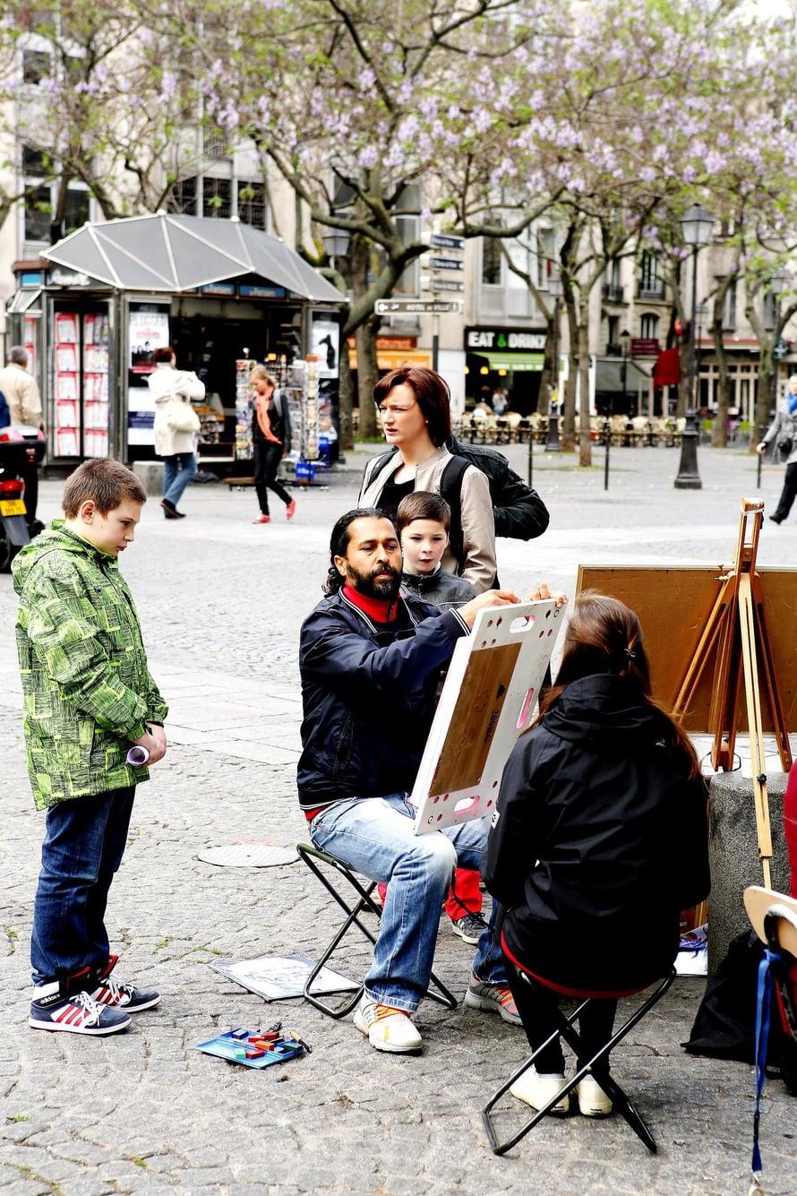 Maalari maalaa Pompidou-keskuksen pihalla.