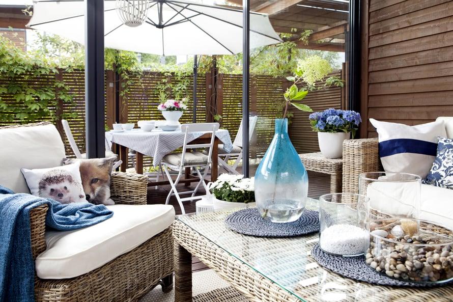 Sinivalkoinen värimaailma on raikas vastakohta punaruskealle laudalle ja vaalelalle rottingille.
