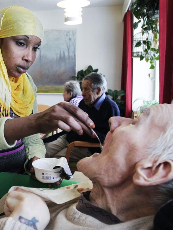 Lähihoitaja Nafra Jusuf työskentelee Kustaankartanon vanhustenkodissa. Tässä hän syöttää Pekka Flikmania.