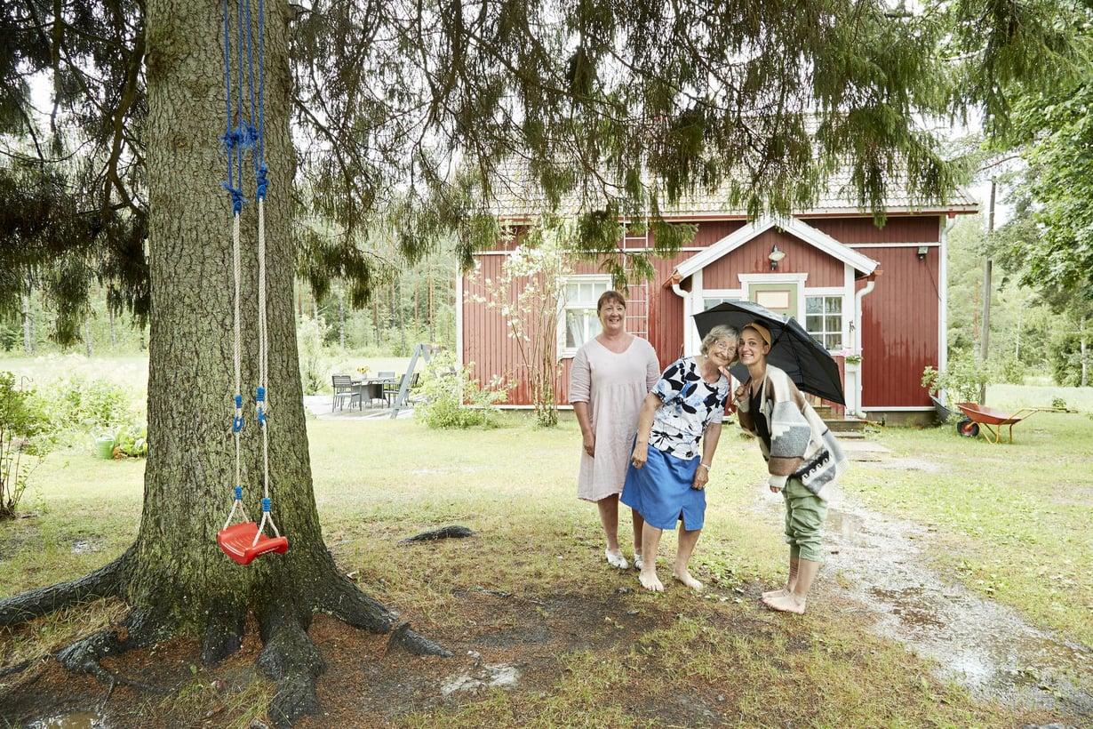 Sari Laakso (vas.), Eliisa Skrifvars ja Krista Laakso pitävät kesäsadetta pihakuusen alla.