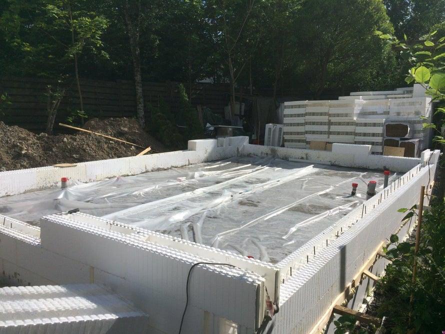Lattialaatta on valettu ja suojattu muovilla, joka hidastaa betonin liian nopeaa kuivumista kesähelteellä.