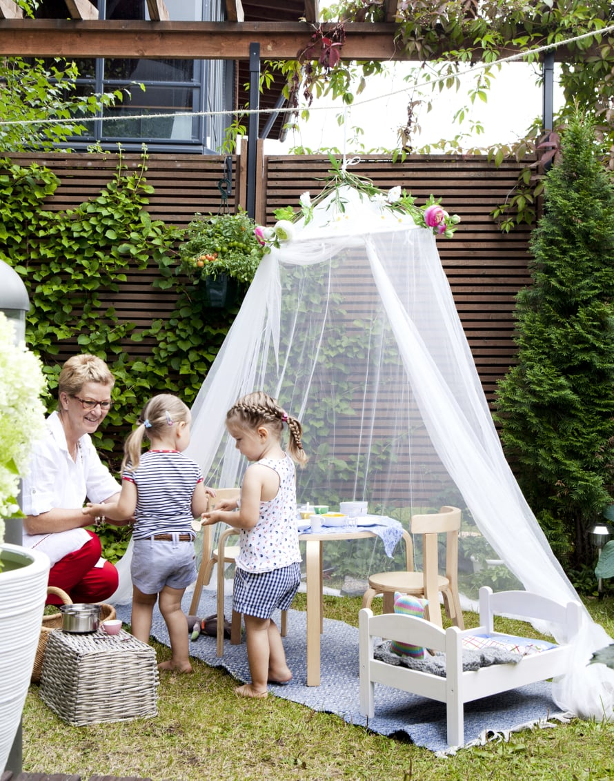 Alisa ja Ellen tarjoavat Anne-mummille kahvia prinsessalinnassa. Kevyt maja on nopea rakentaa, ja sateen sattuessa sen voi siirtää lasitetun terassin suojaan.