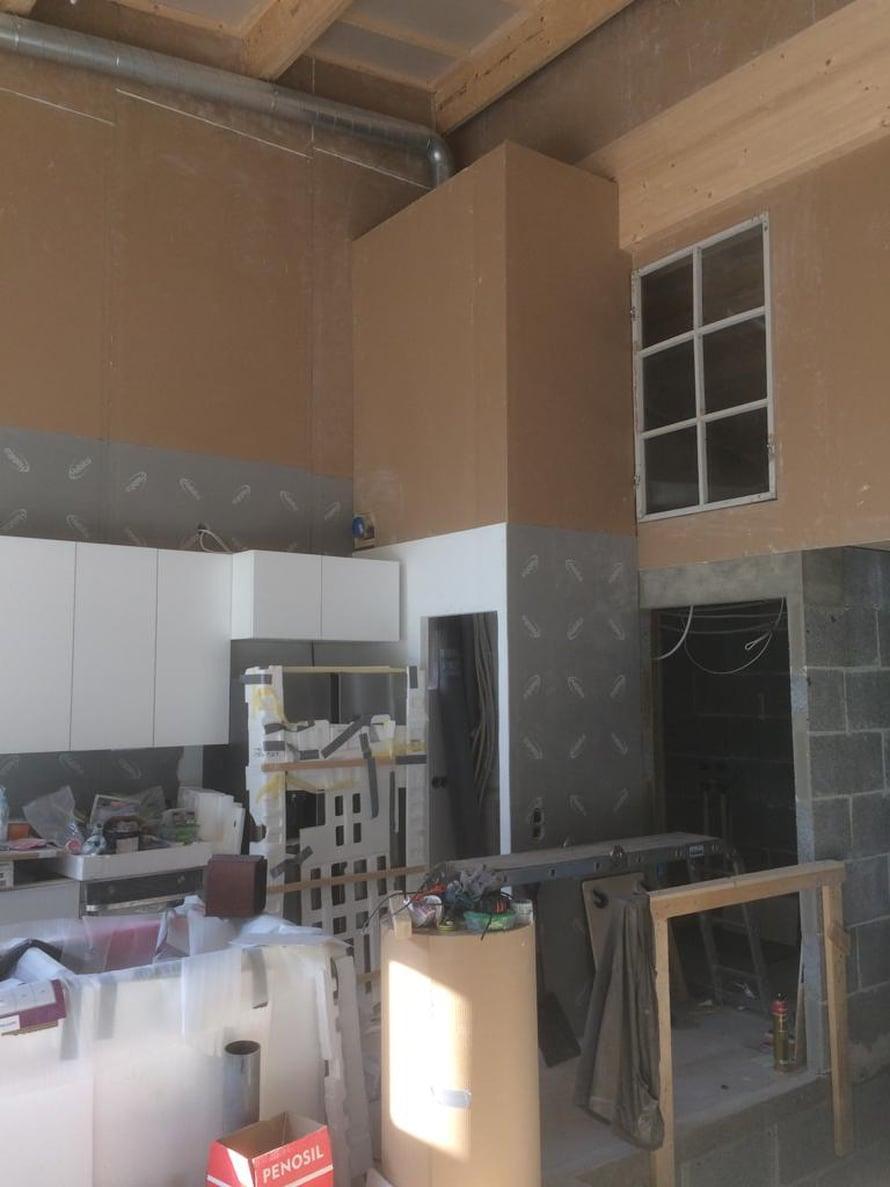 Sisätilat alkavat olla maalausta vaille valmiita. Kuvassa keittiö, ruokavaraston oviaukko ja kierrätetty ikkuna, joka antaa valoa käyttöullakolle.