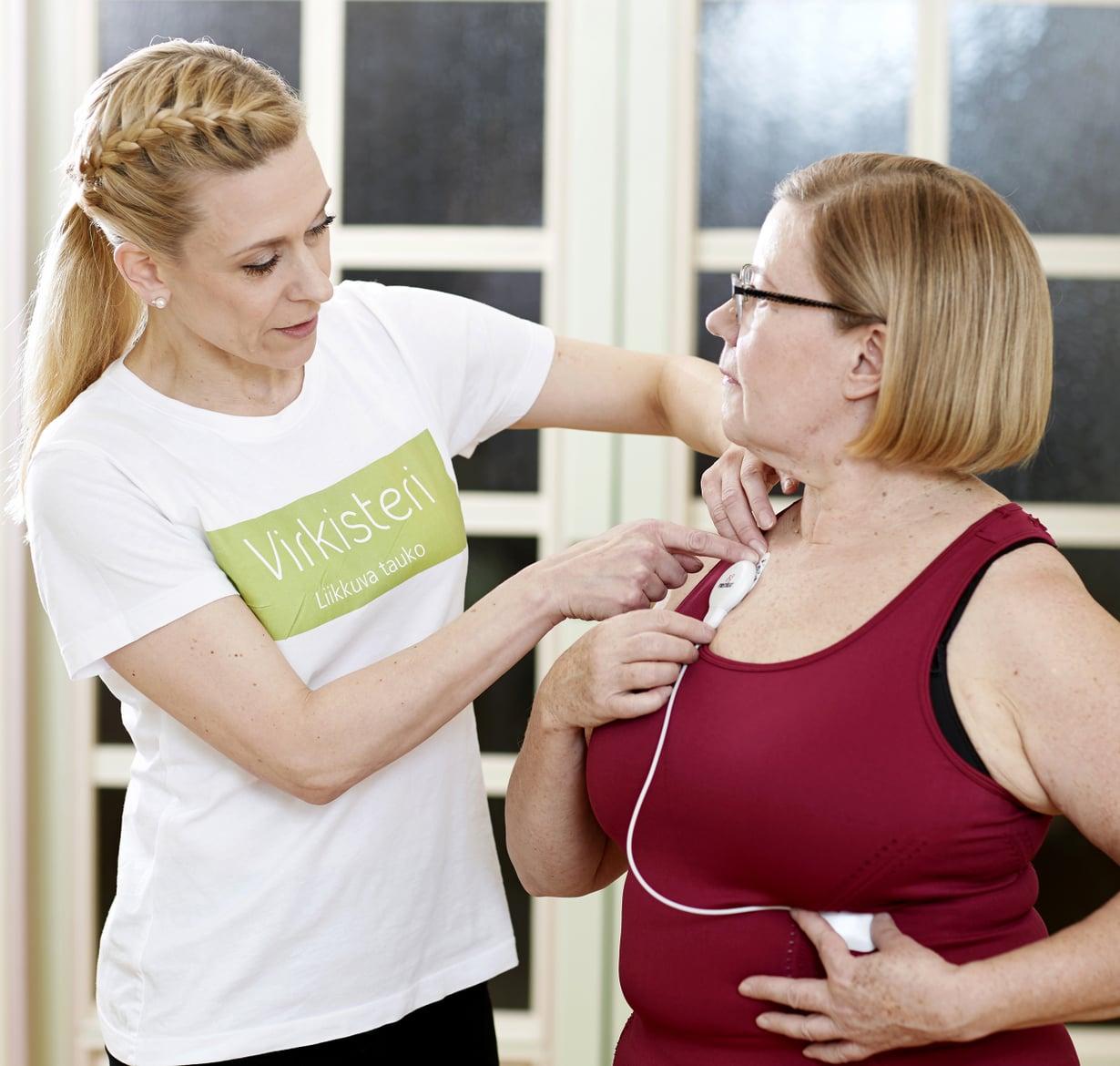 Työfysioterapeutti Riikka Ilmivalta asentaa Pialle Firstbeat-mittarin.