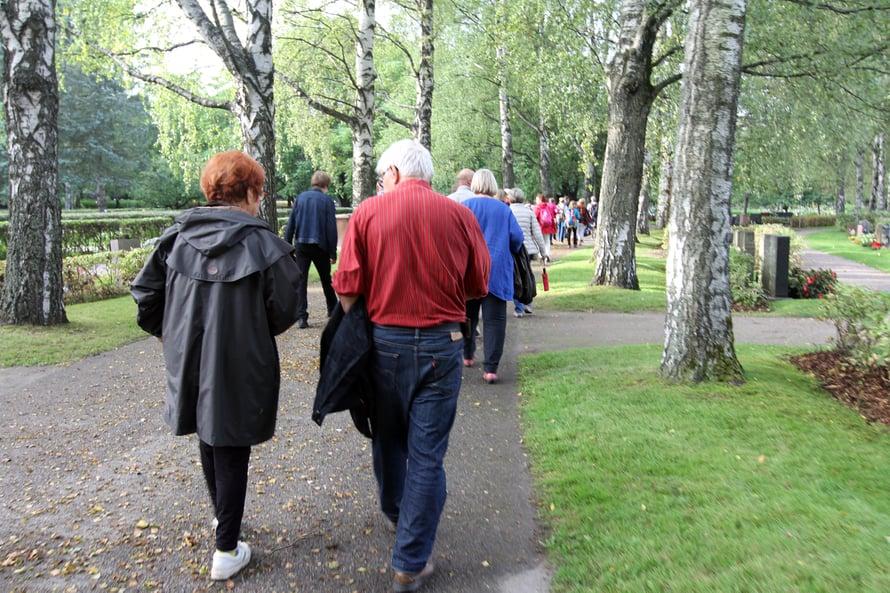 Osallistujajoukko kävelee pappi Risto Alajan perässä Malmin hautausmaalla.
