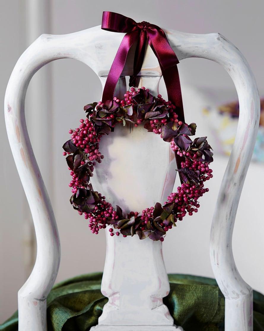 Ruokapöydän tuoli ansaitsee juhla-asun. Silkkinauhalla selkänojaan solmittu seppele on taivuteltu pippurinmarjoista ja hortensian kukinnoista.
