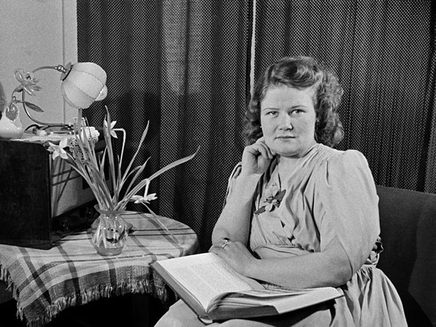 """Nainen istuu kirja sylissään, pöydällä leikkokukkia ja radio, 1940-luku. Kuva: <span class=""""photographer"""">Väinö Kannisto / Helsingin kaupunginmuseo</span>"""