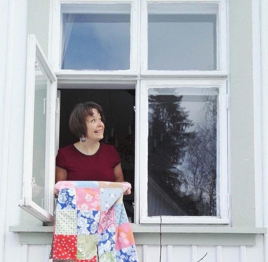 Riikka Kangasmäki kotinsa ikkunassa.