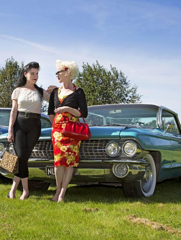 Toisiaan täydentävä kaksikko. Tummatukkaisen Netan sinivalkoinen Oldsmobile Holiday Sedan on vuodelta 1957. Vaalean Lotan auto on Cadillac Sedan Deville vuodelta 1961. Itse he eivät autojaan juuri fiksaile – miehet ovat sitä varten.