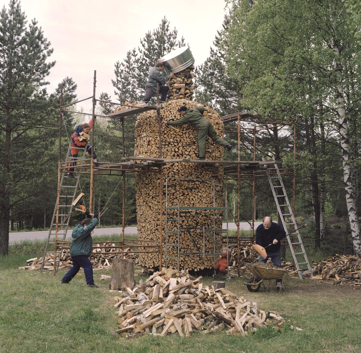 Pekka Turunen ja rakennuskumppanit ahkeroivat vodkapullonm muotoisen pinon parissa.