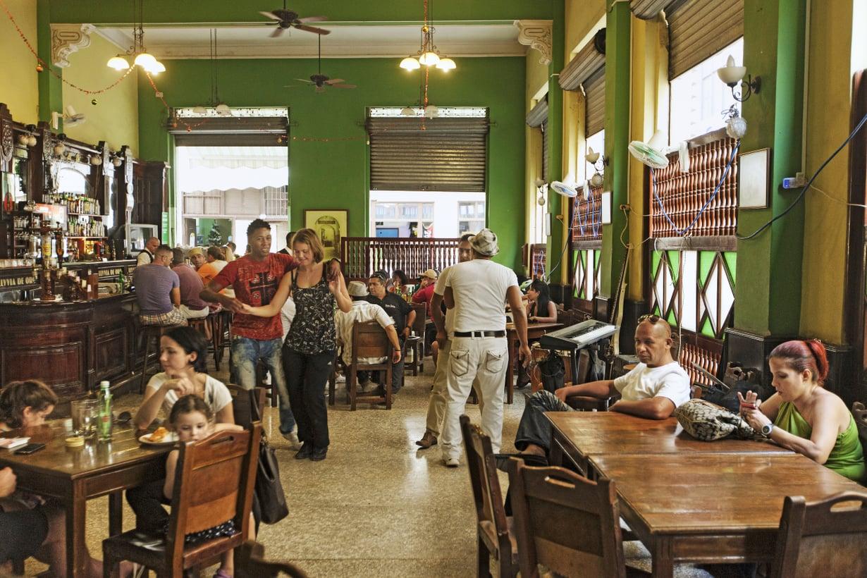 Kuubalaismies tanssittaa turistia levymusiikin tahdissa, kun bändi on tauolla vanhankaupungin Obispo-kadun La Lluvia de Orossa.