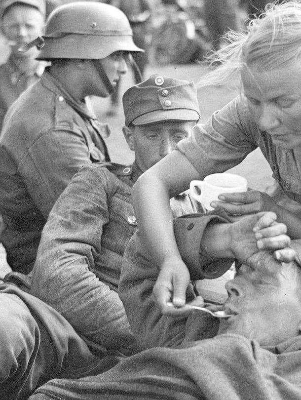 Kiestinki-Tuoppajärvi 15.8.1941. Nuori rintamalotta helpottaa haavoittuneen oloa.