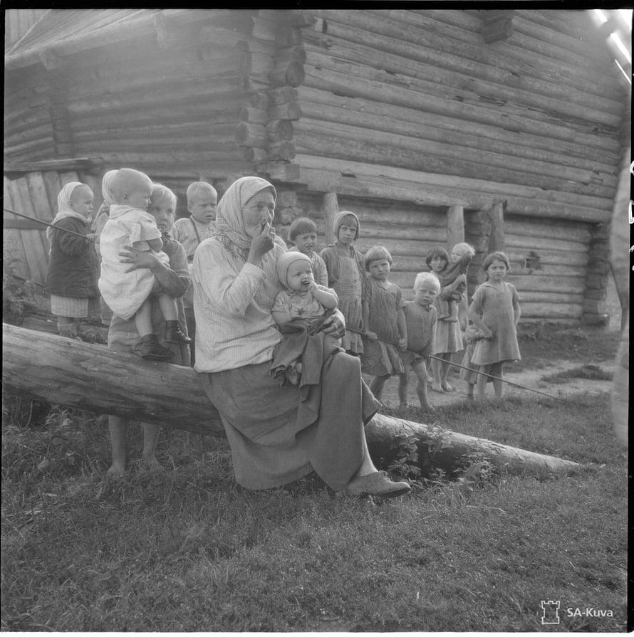 Vanha mummo kertoilee kokemuksiaan Uteliaat lapset ympäröivät. Metsoiniemi 1942.